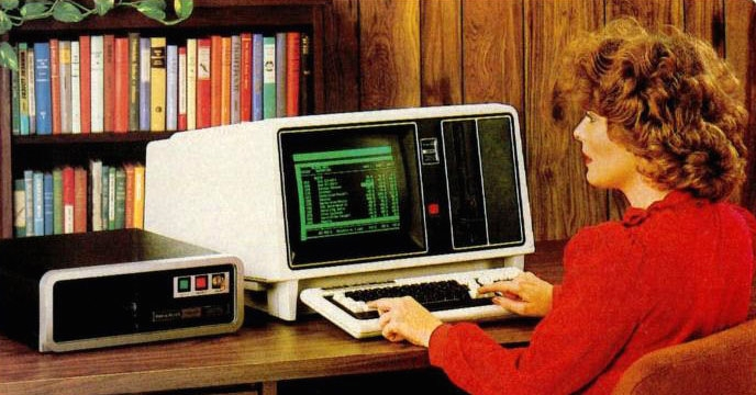 Pictures of women using boxy office computers from the early 1980s