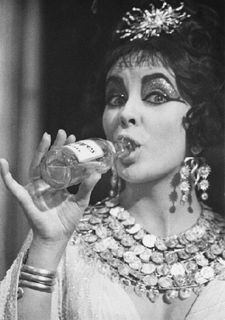 Elizabeth Taylor having a drink on the set of the 1963 film, Cleopatra