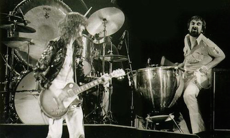 Keith Moon sitting at John Bonham's drum kit while Jimmy Page looks on, June 23rd, 1977