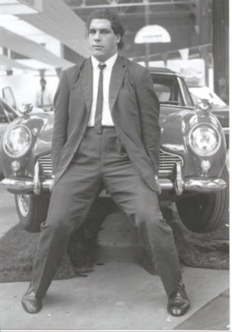 A young André the Giant lifing the front end of a car