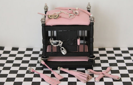 Miniature dollhouse BDSM cage with pink leather cushioning