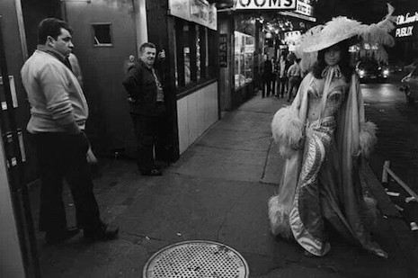 A burlesque dancer outside of a club in the Combat Zone, 1970s