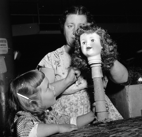 Doll factory working working on a doll head on a stick, 1955