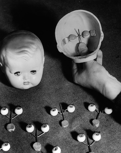 Doll eyes looking at an open doll head at a factory in England, 1949
