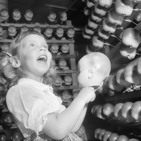 Little girl holding a doll head while others look on, Long Island, 1955