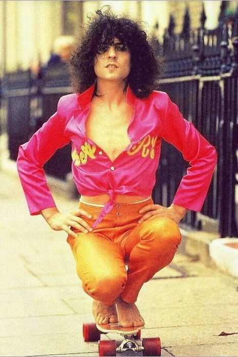 Marc Bolan riding on top of a skateboard