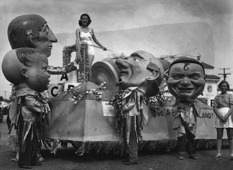 Miss California on her float surrounded by giant papier-mâché masks, mid-1930s