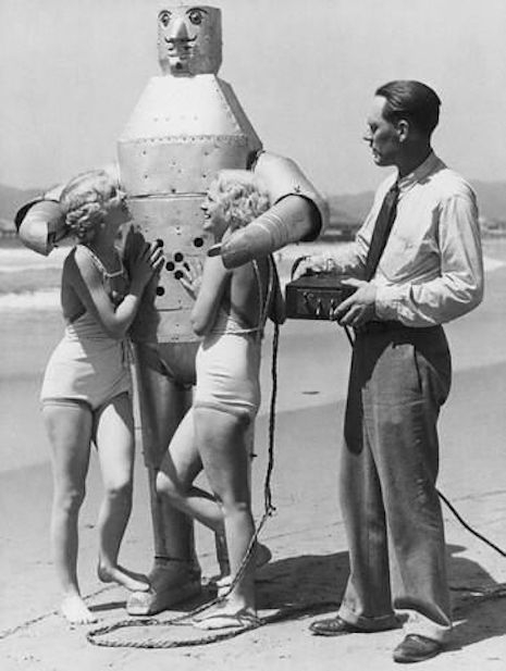 Robot at the beach with two blondes in bathingsuits, late 20s, early 30s