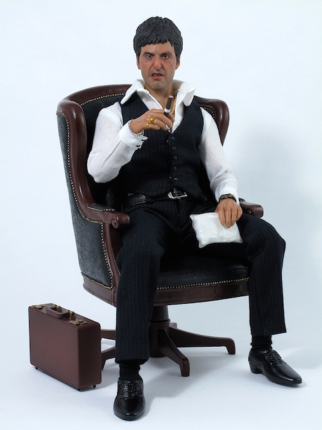 Tony Montana War figure sitting with packages of coke and heroin