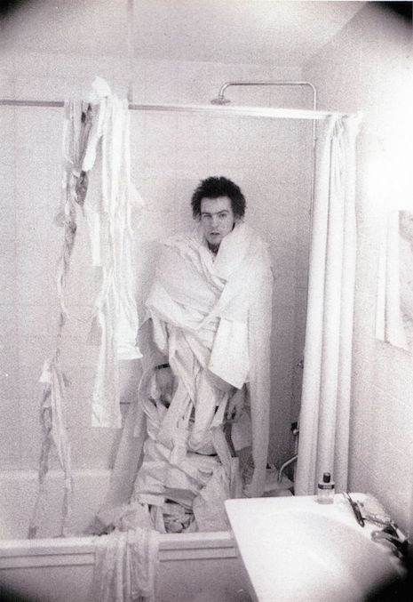 Sid Vicious wrapped in toilet paper in the bathroom shower