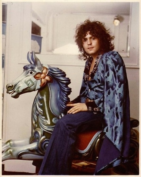 Marc Bolan riding on top of a carousel horse