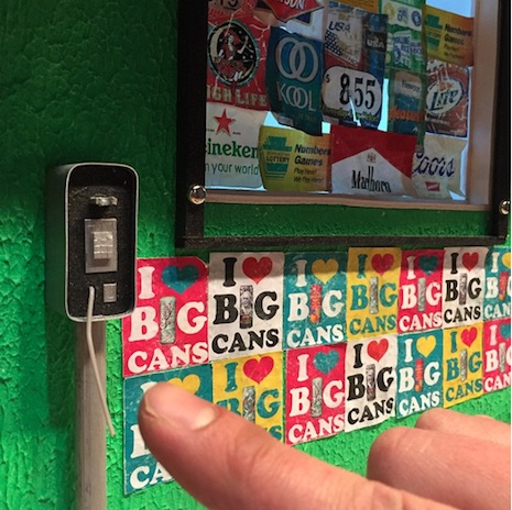 Close up of miniature/phone and stickers (finger for scale)