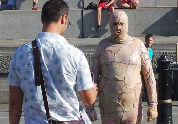 Artist wears chicken flesh gimp suit