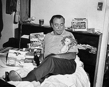 Charles Bukowski in his happy place, in bed drinking with a pretty doll