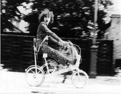 Marc Bolan riding on top of a bike